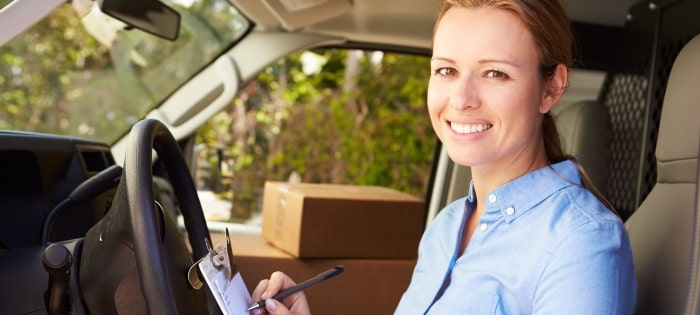 woman-facing-camera-smiling-sitting-in-van-delivering